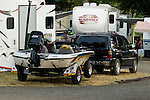 Rear view of Ranger bass boat on the trailer behind a black SUV surrounded by RVs