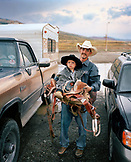 USA, Wyoming, Saddle Bronc Cowboy holding his son, portrait, Cody Rodeo