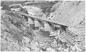 A 3/4 view of RGS Bridge 64-A in Burns Canyon after abandonment.  It was rebuilt in 1912 - 128 feet long and 10 feet high.<br /> RGS  Burns Canyon, CO  Taken by Maxwell, John W. - 8/19/1958