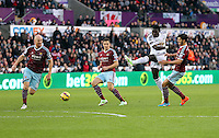 Pictured: Bafetimbi Gomis of Swansea (3rd L) takes a shot off target, against L-R James Collins, Stewart Downing and James Tomkins of West Ham Saturday 10 January 2015<br />