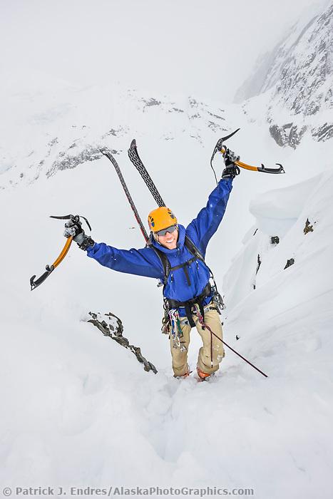 Tim banfield climbs a rocky slope in the Alaska Range mountains, Interior, Alaska.