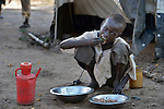 A boy eats in the Gendrassa refugee camp in South Sudan's Upper Nile State. More than 110,000 refugees were living in four camps in Maban County in October 2012, but officials expected more would arrive once the rainy season ended and people could cross rivers that block the routes from Sudan's Blue Nile area, where Sudanese military has been bombing civilian populations as part of its response to a local insurgency. Conditions in the camps are often grim, with outbreaks of diseases such as Hepatitis E.