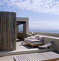 A secluded sun deck on the roof of the beach house with views of the ocean