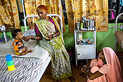 Rajeshwari feeds her 9 month malnutritioned grandson, Raj while her daughter, 19 year old Mira looks on at the 'Nutritional Reahabilitation Centre' at the pediatrics section of Maharani Laxmibai Medical College in Jhansi, Uttar Pradesh, India. The Indian government spends $1.4 billion a year - on programs that include weighing newborn babies, counseling mothers on healthy eating and supplementing meals, but none of this is yeilding results. According to UNICEF, some 48% of Indian children, or 61 million kids, remain malnourished, the clinical condition of being so undernourished that their physical and mental growth are stunted. Photo: Sanjit Das/Panos for The Wall Street Journal.Slug: IMALNUT