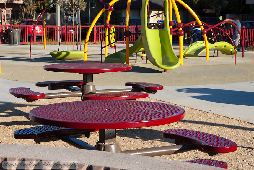 The picnic and play area at Circle Park, a small pocket park in Anaheim, CA.  Visible are tables and play structures.  A few children are visible in the distance.
