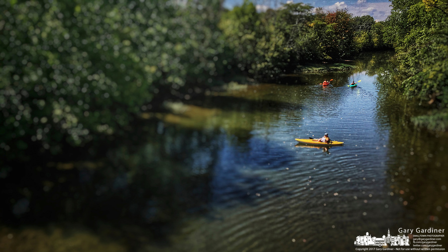 Kayakers enjoy the calm waters of Alum Creek moving through Westerville, Ohio, on n unusually mild August afternoon