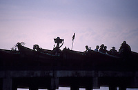 Fishermen, fishing boats and vendors silhouetted by the setting sun on the town pier in La Libertad, El Salvador