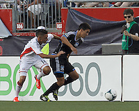 San Jose Earthquakes midfielder Shea Salinas (6) dribbles down the wing as New England Revolution forward Diego Fagundez (14) defends. In a Major League Soccer (MLS) match, the New England Revolution (white) defeated San Jose Earthquakes (black), 2-0, at Gillette Stadium on July 6, 2013.