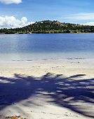 Pernambuco, Brazil. Beach with white sand and the shadow of a palm tree with a coconut palm plantation across the blue lagoon.