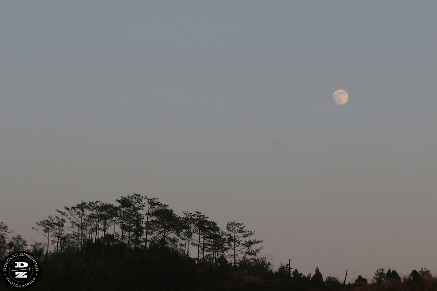 A full moon rises above Heavenly Peak just after sunset and the Wuyi Shan scenic area in Wuyi Shan, China.  Wuyi Shan has some of the most spectacular natural beauty in Fujian province.  Photograph by Douglas ZImmerman