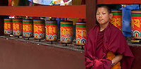 Buddhist monk at prayer wheels in Sikkim, India