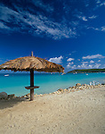 Antigua, West Indies<br /> Thatched beach umbrellas overlooking Dickinson Bay and Weatherills Point