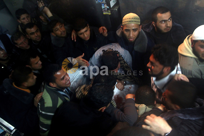 Palestinians mourn in a hospital over the body of one of two militants of the Al Quds Brigades, the military arm of Islamic Jihad, after they were killed in a second Israeli air strike in Gaza City on March 9, 2012, bringing the number of Palestinians killed in a day of cross-boarder fighting to four. The two strikes came in response to two waves of Palestinian mortar fire into southern Israel, in which no casualties were reported. Photo by Ashraf Amra