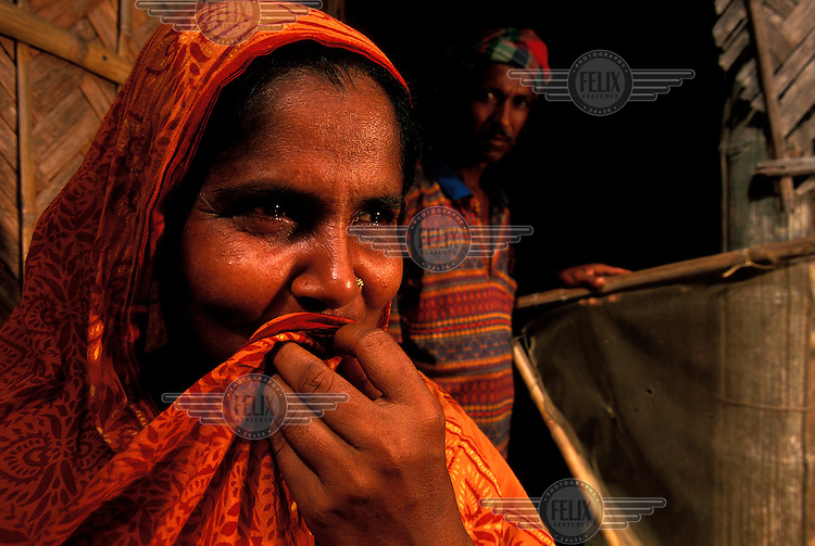 Portrait of Samsoon Nahar (35yrs. old)  and her husband, Yunus Ali.  Mother of two young boys, Samsoon  works in post-harvest rice and seed activities (as do many women in this and similar villages), but, due to her husbands' recurring illness, is forced to also work as a maid in neighbouring households, for food.