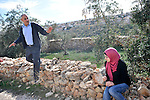 Jamal Amira with his daughter Salaam, backdropped by the Israeli settlement Hashmona'im, in his land in the village of Na'alin, West Bank.