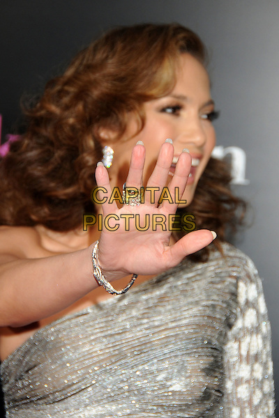 "JENNIFER LOPEZ .""The Back-up Plan"" Los Angeles Premiere held at the Regency Village Theatre, Westwood, California, USA, 21st April 2010..arrivals portrait headshot  hand ring gesture funny bracelet earrings wavy hair one shoulder silver sleeve sheer shiny shimmery .CAP/ADM/BP.©Byron Purvis/AdMedia/Capital Pictures."
