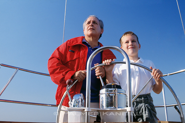 Grandfather and Grandson at helm of sailboat