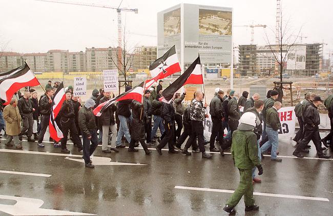 Gegen das in Berlin geplante Holocaustmahnmal rief ein sog. Buendnis gegen das Holocaustmahnmal zu einer Demonstration. 6-700 Skinheads und Rechtsextreme aus dem gesamten Bundesgebiet kamen zu der gerichtlich durchgesetzten Demonstration. Es waren fast ausschliesslich NPD-Mitglieder und Sympathiesanten. Die Organisation der Demonstration lag fest in den Haenden sogenannten Freier Kameradschaften.<br /> Hier: Die Demonstration zieht mit Fahnen in den Farben des Deutschen Reiches vor dem Bauplatz des Mahnmals vorbei.<br /> Berlin, 29.1.2000<br /> Copyright: Christian-Ditsch.de<br /> [Inhaltsveraendernde Manipulation des Fotos nur nach ausdruecklicher Genehmigung des Fotografen. Vereinbarungen ueber Abtretung von Persoenlichkeitsrechten/Model Release der abgebildeten Person/Personen liegen nicht vor. NO MODEL RELEASE! Nur fuer Redaktionelle Zwecke. Don't publish without copyright Christian-Ditsch.de, Veroeffentlichung nur mit Fotografennennung, sowie gegen Honorar, MwSt. und Beleg. Konto: I N G - D i B a, IBAN DE58500105175400192269, BIC INGDDEFFXXX, Kontakt: post@christian-ditsch.de<br /> Bei der Bearbeitung der Dateiinformationen darf die Urheberkennzeichnung in den EXIF- und  IPTC-Daten nicht entfernt werden, diese sind in digitalen Medien nach &sect;95c UrhG rechtlich gesch&uuml;tzt. Der Urhebervermerk wird gemaess &sect;13 UrhG verlangt.]