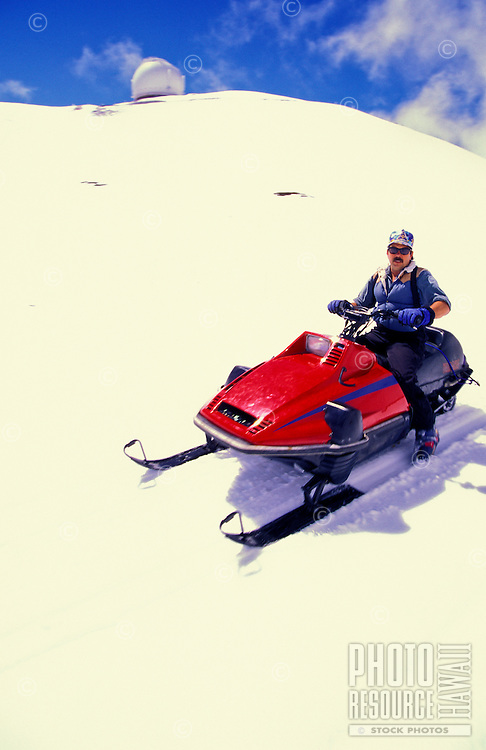 Woman on snowmobile at the summit of Mauna Kea crater with observatory in rear