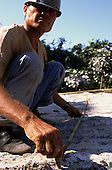 Rio de Janeiro, Brazil. Silva Areal quarry; worker in hard hat measuring rock using a wooden folding rule.