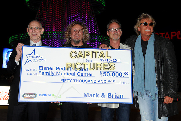 Carl Coan, President CEO of Eisner Pediatric, Sammy Hagar, Mark Thompson, Brian Phelps, 95.5 FM KLOS DJs, Michael Roth, AEG VP of Communications. .AEG Season of Giving Honors Eisner Pediatric & Family Medical Center with Check Presentation held at Nokia Plaza L.A. Live. Los Angeles, California, USA, .15th December 2011.Half length cheque money  .CAP/ADM/BP.©Byron Purvis/AdMedia/Capital Pictures.