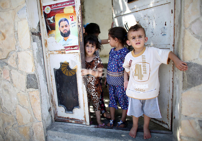 Relatives of Palestinian prisoner in Israeli jails Mohammad Allan, stand next to his  portrait at the entrance of his house in the village of Ainabos, south of Nablus in the occupied West Bank, on August 9, 2015. The Israeli military prosecutor intends to request court permission on Saturday to force-feed hunger striking prisoner Mohammad Allan, the Palestinian minister of prisoner affairs, Issa Qaraqe announced on Friday. Allan, a lawyer from the occupied West Bank city of Nablus, has been on hunger strike for at least 50 days in protest of his detention without charge or trial since his arrest in November. Photo by Ahmad Talat