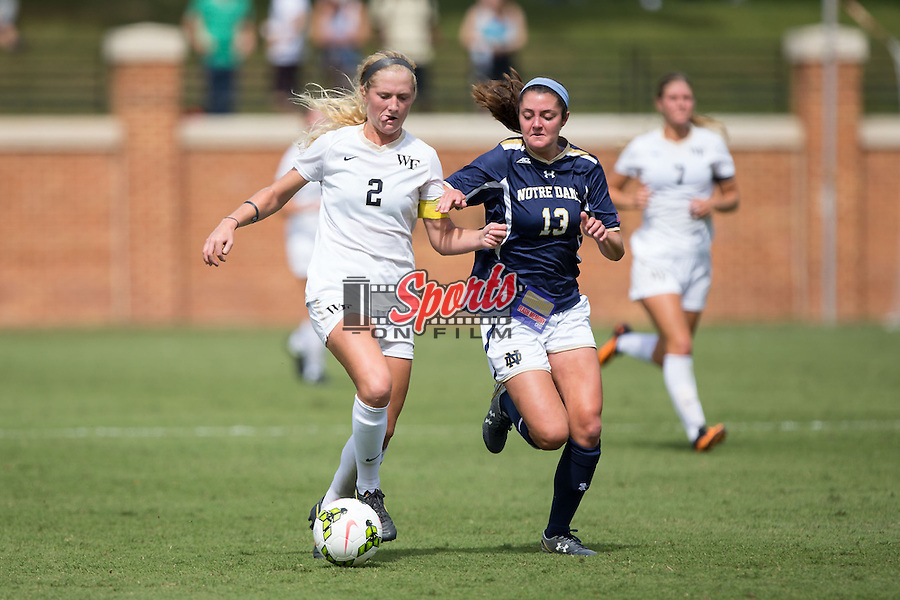 Riley Ridgik (2) of the Wake Forest Demon Deacons keeps the ball away from Ginny McGowan (13) of the Notre Dame Fighting Irish at Spry Soccer Stadium on September 28, 2014 in Winston-Salem, North Carolina.  The Fighting Irish defeated the Demon Deacons 1-0.   (Brian Westerholt/Sports On Film)