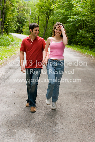 Young couple walking down country road holding hands