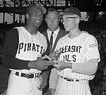 Pittsburgh PA:  Roberto Clemente presenting a trophy to local baseball player from Pleasant Hills before the annual HYPO game at Forbes Field. The money raised by HYPO (Help Young Players Organize) was used to help local communities buy equipment and build ball fields.<br /> Big Jim Daniell, former star college and professional football player is in the background. Daniell Sapp and Boorn did the Public Relations for the HYPO charity baseball game with the Cleveland Indians - 1965