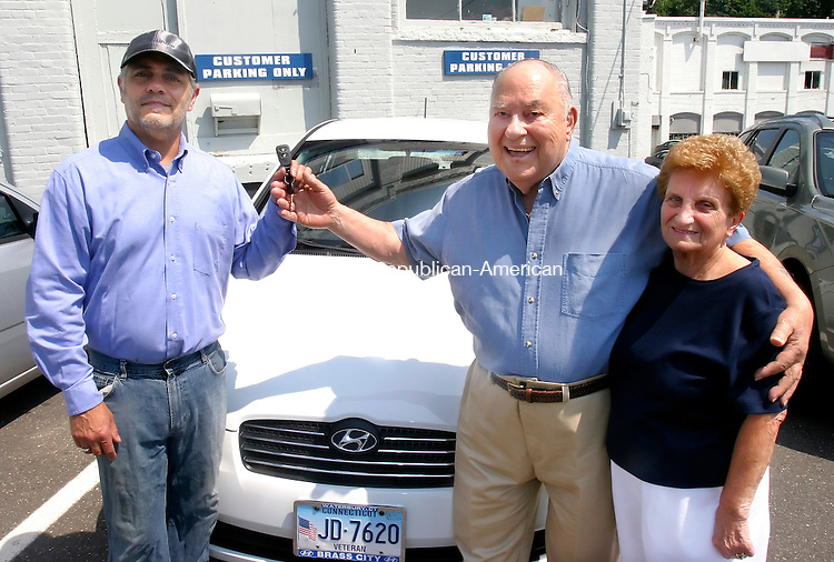 WATERBURY, CT. 02 July 2008-070208SV01--Frank Devino,  co-owner of  Brass City Hyundai on 480 Watertown Ave. hands Joseph Cammelletta and his wife Carmella of Waterbury the keys to their new Hyundai in Waterbury Wednesday, Cammelletta was the winner of the I AUTO WIN Contest sponsored by the Republican-American.Steven Valenti Republican-American