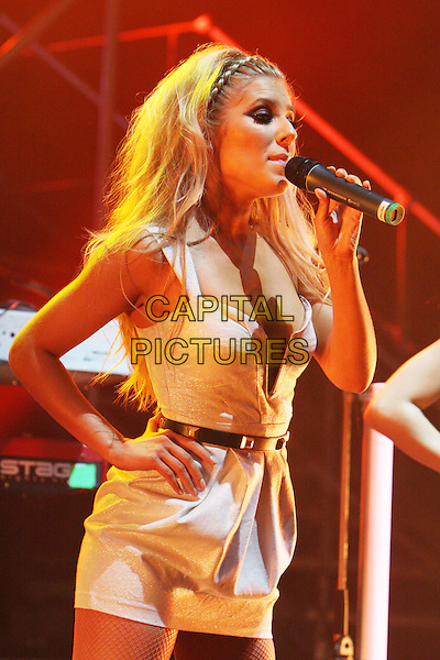 THE SATURDAYS - Mollie King.Live in concert at the Hammersmith Apollo, London, England..June 24th, 2009.stage gig performance performing music half length white cream dress belt hand on hip singing side view plunging neckline .CAP/MAR.© Martin Harris/Capital Pictures.