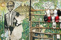 Senegal. Dakar. On the wall of the french cultural center (CCF), Adidas sport caps for sale. Colorful painting in fresco of Leopold Sedar Senghor, who was a politician, a writer and the first senegalese president after french colonialism. Leopold Sedar Senghor is wearing the official uniform of a member at the french Académie, known as l'habit vert, or the green habit. The habit vert, worn at the Académie's foreign ceremonies, consists of a long black coat heavily-embroidered with golden-green leafy motifs, together with black trousers. African village's huts. 10.12.09  © 2009 Didier Ruef