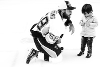 Kris Letang #58 of the Pittsburgh Penguins talks to his son following their 3-1 win against the San Jose Sharks during game six of the Stanley Cup Final at SAP Center in San Jose, California on June 12, 2016. (Photo by Jared Wickerham / DKPS)