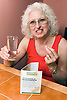 Woman taking medication for osteoporosis with a glass of water,