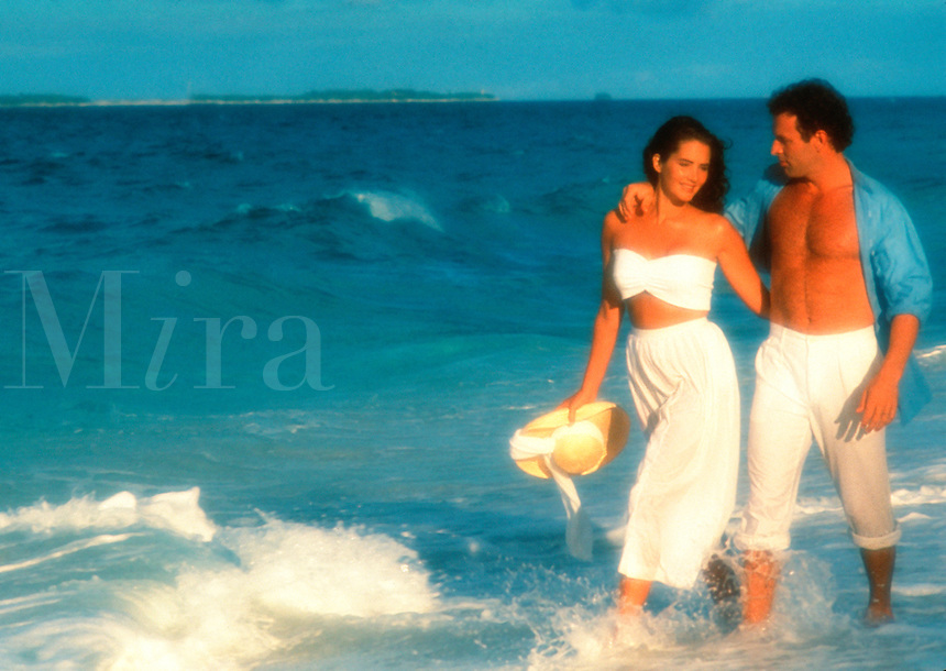 Soft-focus couple in white walking on beach