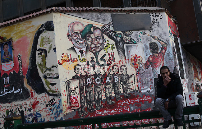 A Egyptian sits at the presidential palace and anti-Morsi graffiti is seen on the palace's wall behind him in Cairo, Dec. 18, 2012. Egypt's opposition staged rallies across the country on Tuesday to protest against the draft constitution referendum, after the country's Ministry of Justice ordered a probe into allegations of widespread voting irregularities during Saturday's first round of voting on the document. Photo by Ashraf Amra