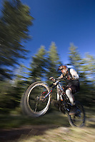 Dave Fafard pop a wheelie on mountain bike, Alberta, Canada
