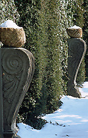 Carved pedestals with snow-filled urns line the path bedside a high hedge