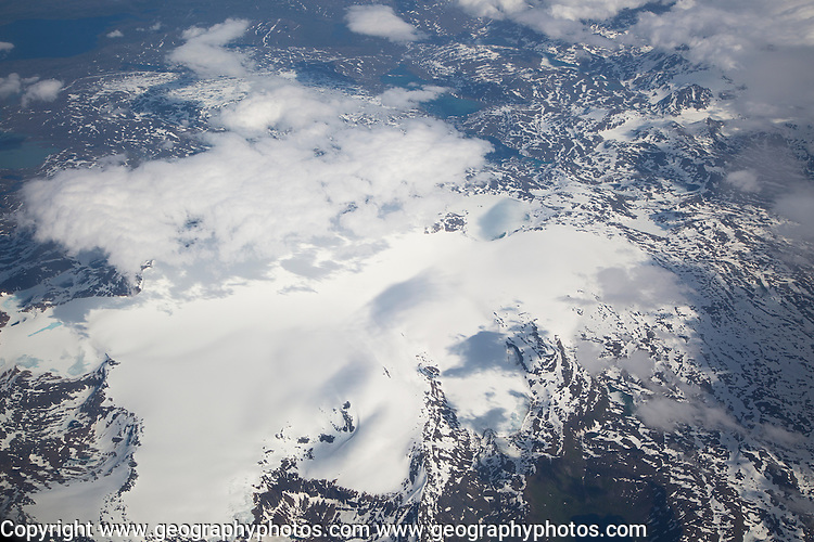 Broken cumulus cloud seen from above looking down over snow covered mountains, western Norway