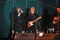 Peter Noone holding an old album cover of his likeness next to his face while singing at the Hamden Free Summer Concert Series, July 2009.
