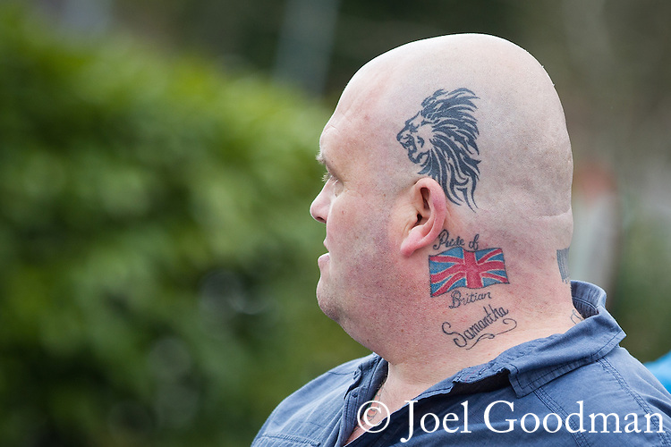 "© Joel Goodman - 07973 332324 . 04/05/2013 . Leeds , UK . An EDL supporter with a tattoo reading "" Pride of Britian "" [sic] . The English Defence League hold a demonstration in the Moortown housing estate in Leeds over plans to convert a disused pub in to an Islamic Centre . This is the first EDL demonstration in the region since six men were convicted of planning a terrorist attack on an EDL demonstration in Dewsbury . Photo credit : Joel Goodman"