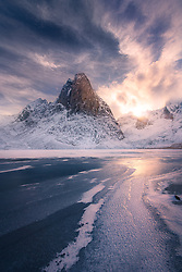 A natural S-curve created by ice and blowing snow lead to a beautiful sunstar and colorful sky behind Shark's Tooth, reflected in a frozen lake beneath.