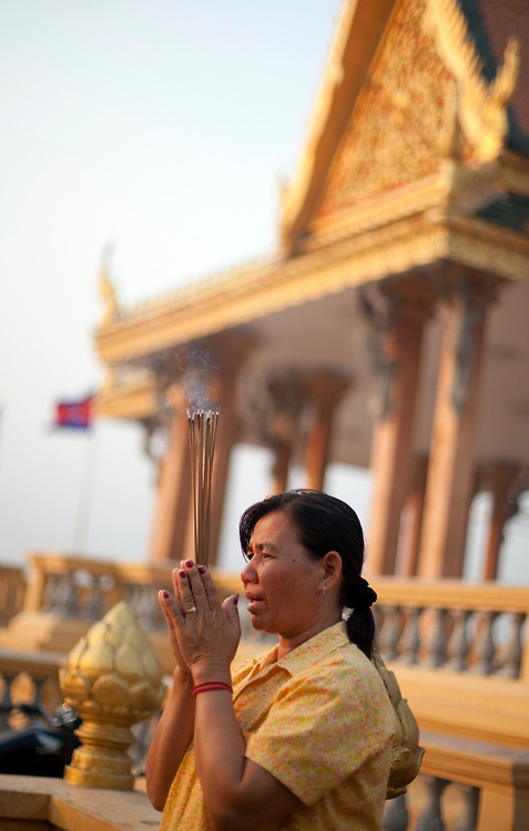 Cambodians pray at a small shrine next to the Mekong River in Phnom Penh, Cambodia. <br /> <br /> Photos &copy; Dennis Drenner 2013.