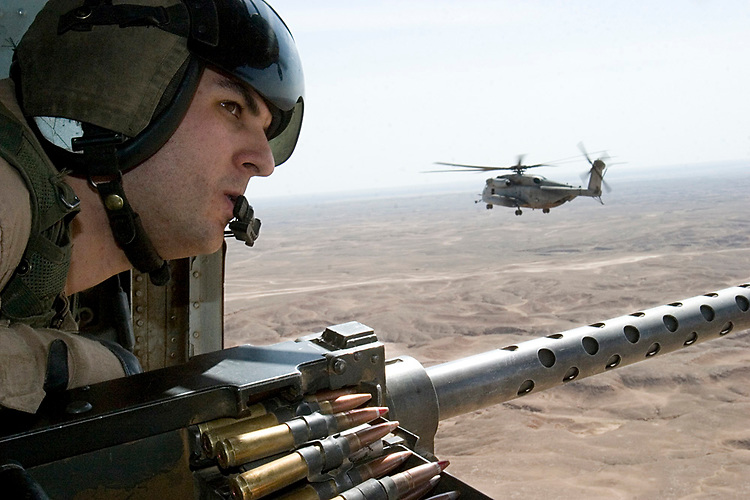 10 April 2007, Cpl. Peter J. Ramos from Marine Heavy Helicopter Squadron 465, provides security with a M2 .50 Caliber Machine Gun in a Cargo Helicopter 53 Echo while in route to Camp Al Asad, Iraq to pick up Meals Ready to Eat (MREs) to be delivered to Combat Outpost Timberwolf. HMH 465 is deployed with Multi National Forces-West in support of Operation Iraqi Freedom in the Al Anbar province of Iraq to develop Iraqi Security Forces, facilitate the development of official rule of law through democratic reforms, and continue the development of a market based economy centered on Iraqi reconstruction. (Official USMC photograph by Cpl. Shane S. Keller)