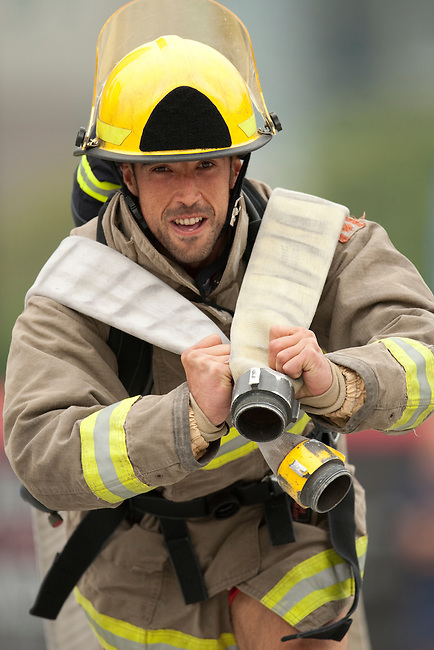 Vancouver, Canada, Aug 6th 2009.  World Police and Fire Games, Ultimate Firefighter Competition. Competitor Israel Huerta Zarza from the Madrid Fire Department, Spain, pulls hard during the Hose Task portion of the competition. In this stage, competitors must drag two 150-foot long 2 ½-inch fire hoses their full length plus 30 feet, and then move to another station and roll up two 50-foot sections of hose and carry them back to the finish line.  Israel finished 14th in the senior A (ages 30-34) division, with a combined time of 5:23.06 in the four stages.  Photo by Gus Curtis