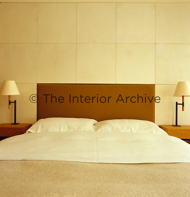 The headboard is incorporated into the wall covering of the Zen-like bedroom