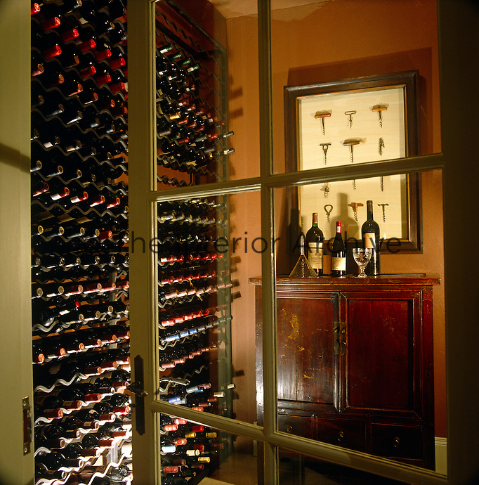 Wine racks are arranged from floor to ceiling in this well-stocked cellar where a collection of framed antique corkscrews is displayed above a mahogany cupboard