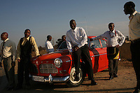 JOHANNESBURG, SOUTH AFRICA - JULY 19:  Men gather by a classic Volvo car in Johannesburg, South Africa.  (Photo by Landon Nordeman)