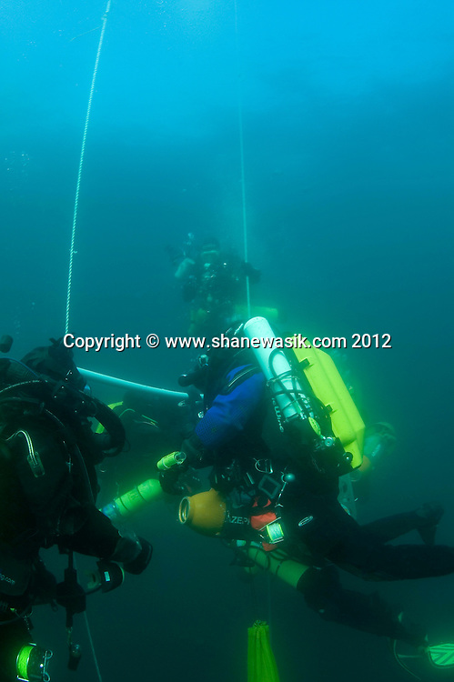 a team of technical divers decompress after a deep trimix wreck dive