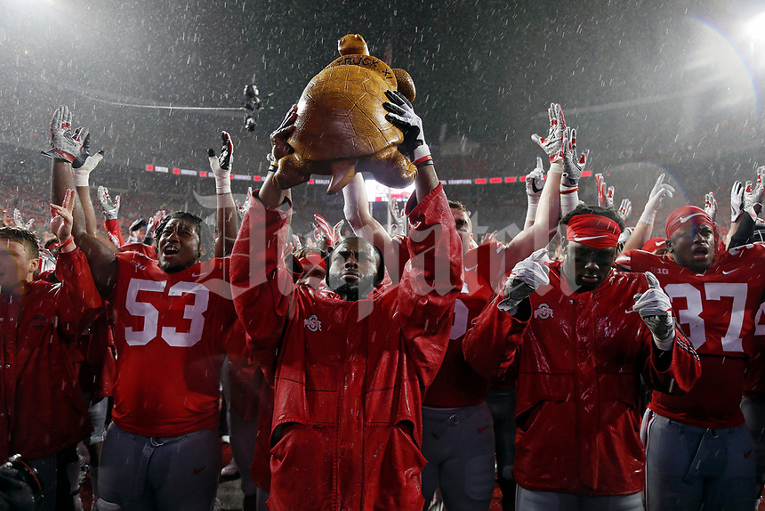 Ohio State Buckeyes quarterback J.T. Barrett (16) holds up the carved wooden Illibuck Trophy after beating Illinois Fighting Illini 52-14 after their game at Ohio Stadium on November 18, 2017.  [Kyle Robertson / Dispatch]